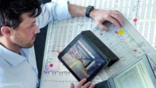 Auswertung der Analyseergebnisse des Safety Scans mit Tablet, Computer und Dokumenten