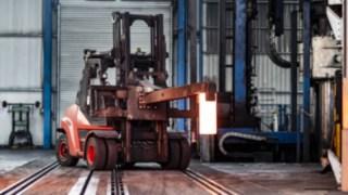 Das Gerät transportiert ein glühendes Eisen über das Gelände.