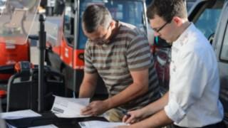 Linde Mietarbeiter geht mit Johannes Kratzel das Übergabeprotokoll für Mietstpler durch
