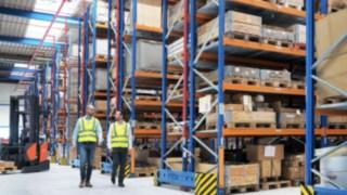 Mitarbeiter von Yanmar Compact Equipment Europe laufen durch das neue Logistikzentrum, das von Linde Material Handling geplant wurde.