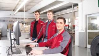 Drei Mitarbeiter von Linde Material Handling arbeiten zu dritt vor einem Computer in einer Werkstatt