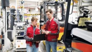 Zwei Mitarbeiter von Linde Material Handling arbeiten in einer Werkstatt an einem Laptop