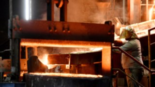Mitarbeiter der Gegengewichtproduktion von Linde Material Handling vor dem Kupolofen
